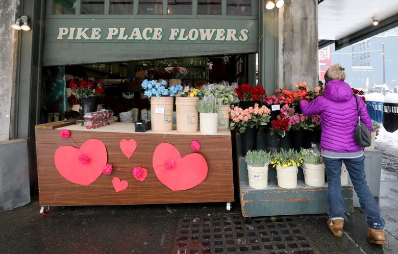 Pike Place Flowers is a bright spot in the Pike Place Market the day before Valentine's Day. (Alan Berner / The Seattle Times)