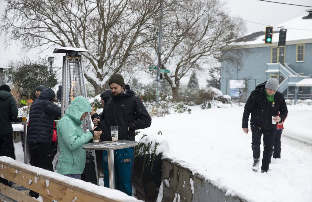 Snow didn't stop anyone from grabbing a beer on the outdoor patio at RidgeWood Bottle & Tap on Saturday. (Amanda Snyder / The Seattle Times)