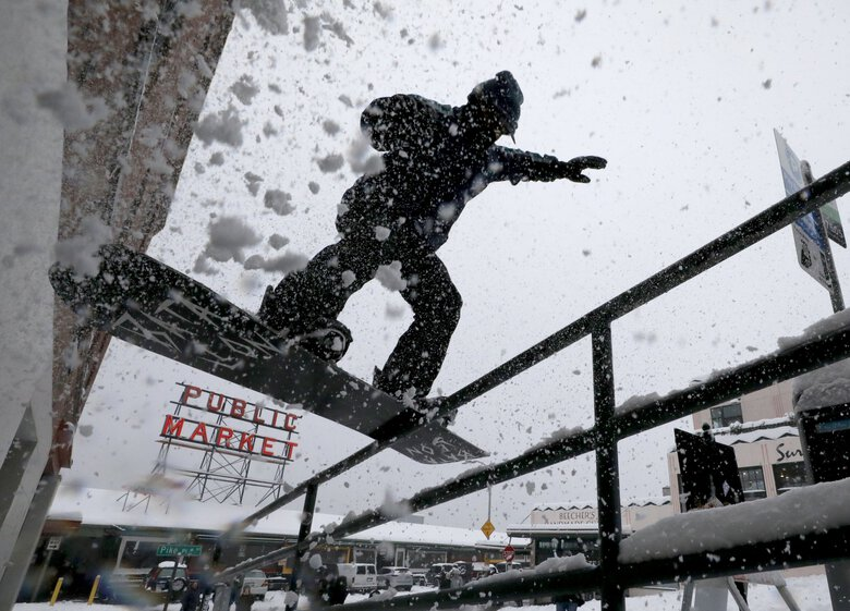 With Pine Street to the Pike Place Market closed, Max Djenohan uses a handrail for snowboarding tricks on Saturday. He had friends make sure no pedestrians were in the path down Pine Street. (Alan Berner / The Seattle Times)