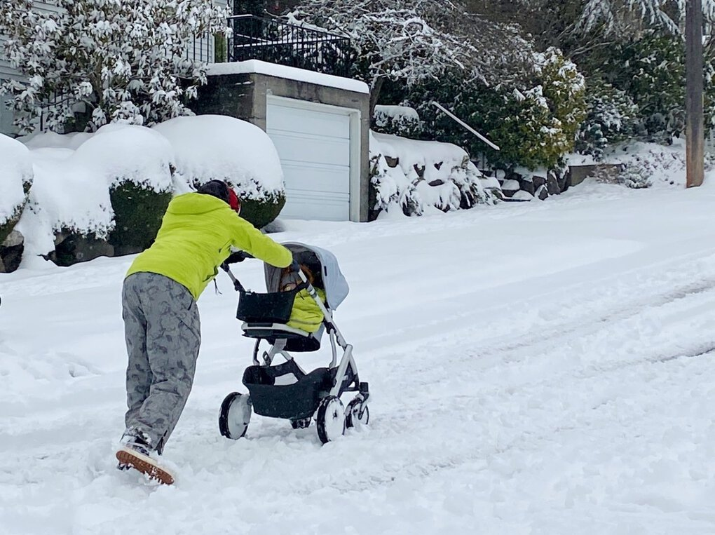 A woman has to lean into her baby stroller to get up NW 59th Street in the Ballard neighborhood of Seattle mid-day Saturday, February 13, 2021.  (Ann Hopping Nelson / Special to The Seattle Times)