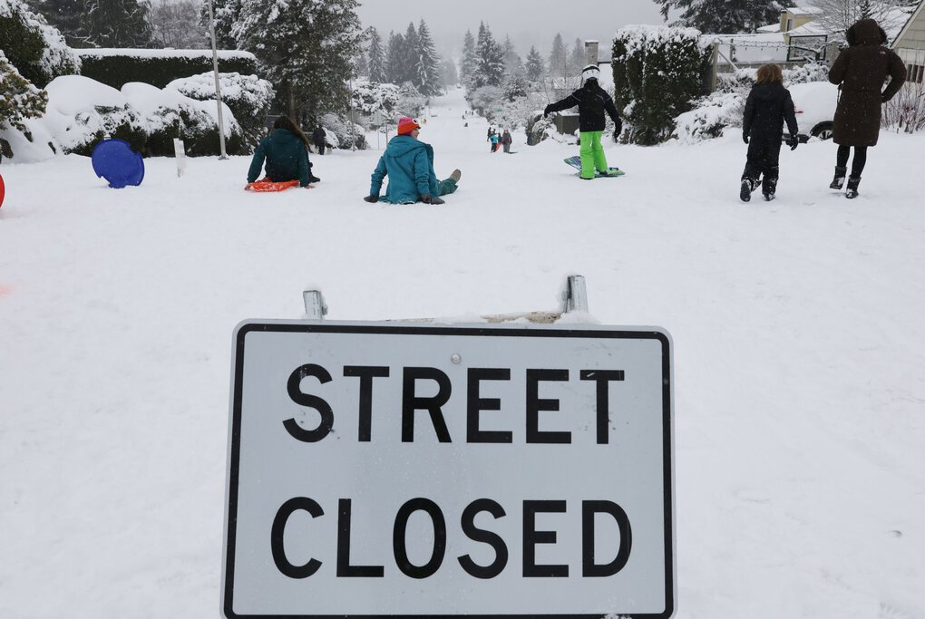It doesn't say closed to sledding, as people enjoy the descent of NE 70th St. at 50th Ave. NE, with more snow coming down to add to the blanket already coating Seattle, Sunday, Feb. 14, 2021. (Ken Lambert / The Seattle Times)