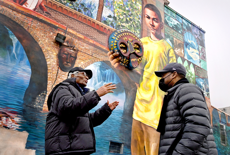 Joe Ligon, left, takes a tour of his new neighborhood with John Pace, a former juvenile lifer himself who works as a reentry coordinator for the Youth Sentencing & Reentry Project. The mural was created by inmates from the now-shuttered Graterford prison, where Ligon and Pace served time together. (Washington Post photo by Michael S. Williamson)