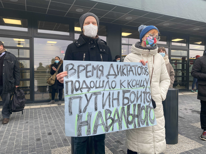 """Ekaterina Raykova-Merz and Andreas Merz-Raykov wait outside Berlin airport Terminal 5 for Navalny to arrive. Their sign reads """"The time of dictators has come to an end. Putin is afraid of Navalny."""" (Washington Post photo by Loveday Morris)."""
