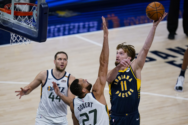 Indiana Pacers forward Domantas Sabonis (11) shoots over Utah Jazz center Rudy Gobert (27) during the second half of an NBA basketball game in Indianapolis, Sunday, Feb. 7, 2021. (AP Photo/Michael Conroy)