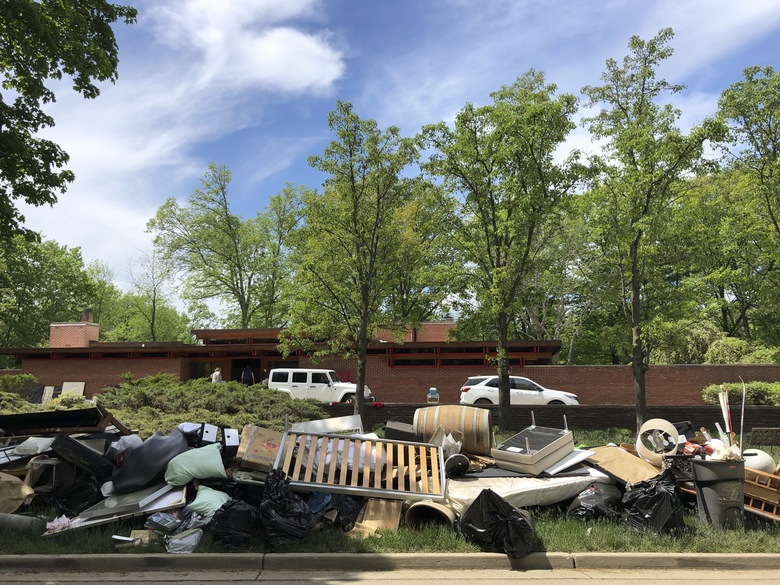 Piles of household debris line Valley Drive in Midland, Michigan, on Wednesday, May 27, 2020. The Michigan Dam Safety Task Force on Wednesday, Feb. 3, 2021 delayed sending the governor its final recommendations, which include increased monitoring of dams and other risk reduction measures. (AP Photo/Tammy Webber, file)