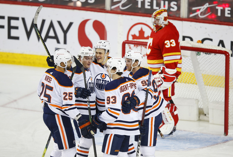 Edmonton Oilers Jesse Puljujarvi (13) celebrates his goal with teammates Darnell Nurse (25), Tyson Barrie (22), Ryan Nugent-Hopkins (93) and Connor McDavid (97) as Calgary Flames goalie David Rittich looks on during the first period of an NHL hockey game, Friday, Feb. 19, 2021 in Calgary, Alberta. (Todd Korol/The Canadian Press via AP)