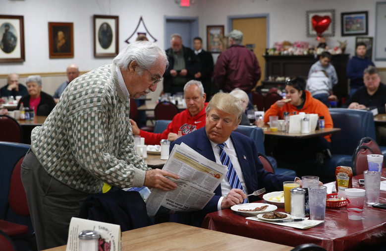 FILE – Republican presidential candidate Donald Trump looks at a newspaper with a diner at Tommy's Country Ham House, Tuesday, Feb. 16, 2016, in Greenville, S.C. For decades, Tommy's Country Ham House has hosted presidential candidates testing their mettle among voters in South Carolina. But the Greenville landmark has announced that it is turning off the fryer and shutting its doors. Owner Tommy Stevenson announced Sunday, Jan. 31, 2021 that Tommy's would close this spring. (AP Photo/Paul Sancya, file)