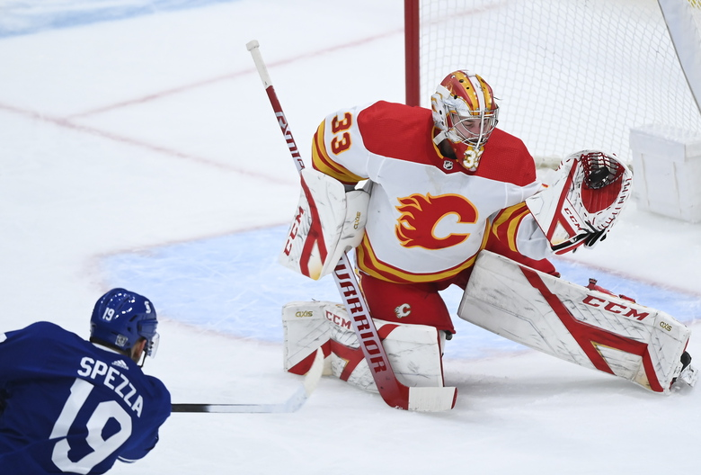 Calgary Flames goaltender David Rittich (33) makes a glove-save against Toronto Maple Leafs center Jason Spezza (19) during second-period NHL hockey game action in Toronto, Monday, Feb. 22, 2021. (Nathan Denette/The Canadian Press via AP)