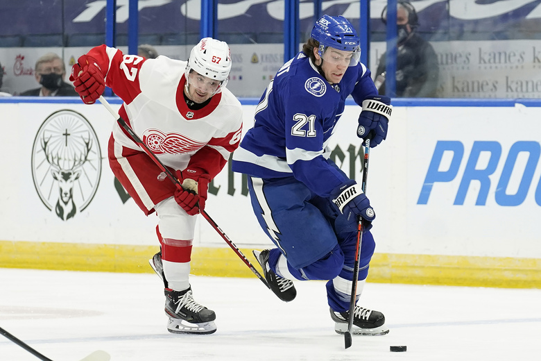 Tampa Bay Lightning center Brayden Point (21) beats Detroit Red Wings left wing Taro Hirose (67) to a loose puck during the second period of an NHL hockey game Wednesday, Feb. 3, 2021, in Tampa, Fla. (AP Photo/Chris O'Meara)