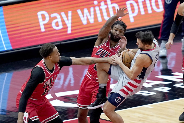 Chicago Bulls' Daniel Gafford, left, and Coby White stop Washington Wizards' Raul Neto from driving to the basket during the first half of an NBA basketball game Monday, Feb. 8, 2021, in Chicago. (AP Photo/Charles Rex Arbogast)
