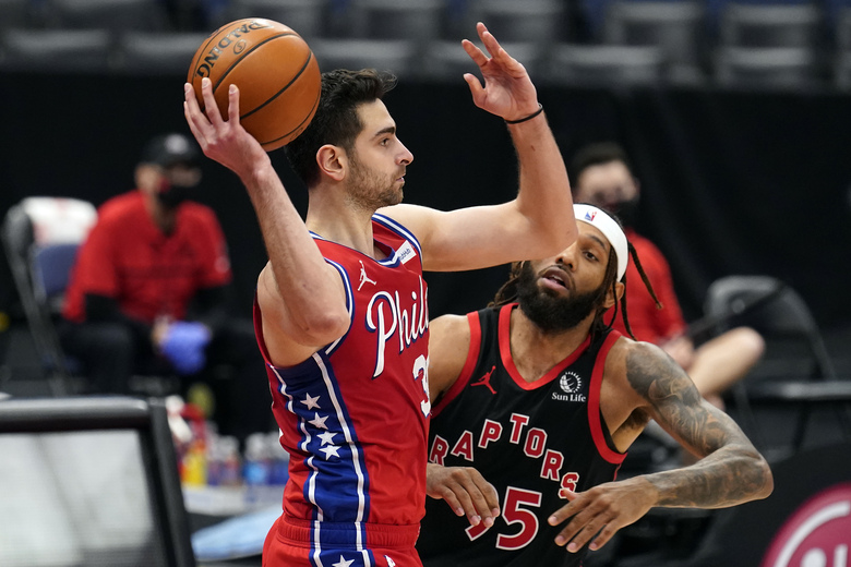 Philadelphia 76ers guard Furkan Korkmaz (30) looks to pass in front of Toronto Raptors forward DeAndre' Bembry (95) during the second half of an NBA basketball game Tuesday, Feb. 23, 2021, in Tampa, Fla. (AP Photo/Chris O'Meara)