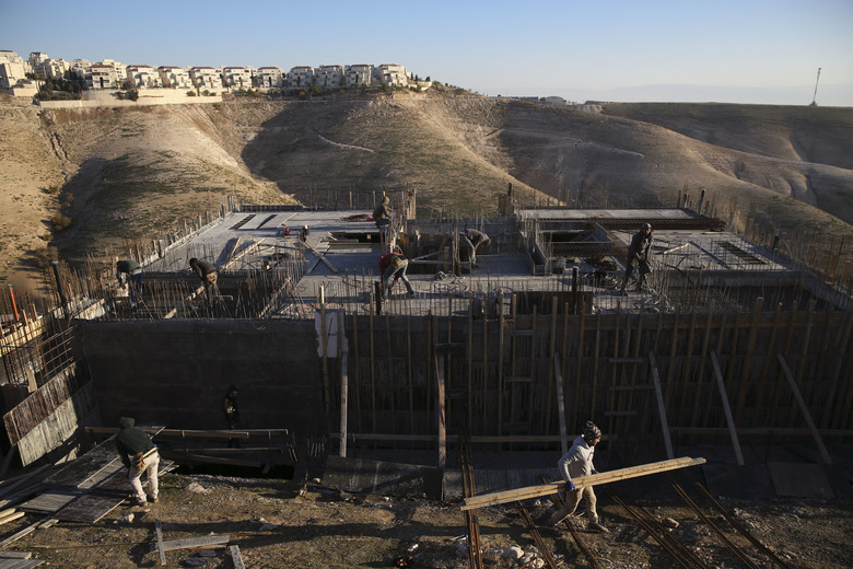 FILE – In this Feb. 7, 2017 file photo, Palestinian laborers work at a construction site in the Israeli settlement of Maale Adumim, near Jerusalem. International Criminal Court's decision authorizing its chief prosecutor to open a war crimes investigation against Israel could soon be reverberating in the Israeli-occupied West Bank. While any potential probe could look at Israeli military campaigns in the Gaza Strip, Israel's half-century campaign of building settlements on occupied lands appears to be especially vulnerable to prosecution. (AP Photo/Oded Balilty, File)