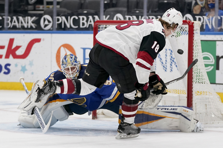 Arizona Coyotes' Christian Dvorak (18) scores the game-winning goal past St. Louis Blues goaltender Jordan Binnington during a shootout of an NHL hockey game Monday, Feb. 8, 2021, in St. Louis. (AP Photo/Jeff Roberson)
