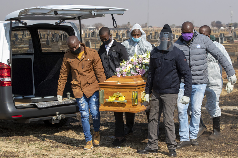 FILE – In this  July 23, 2020, file photo, family members and funeral workers in protective clothing carry the coffin of nurse Duduzile Margaret Mbonane who died from COVID-19, at her funeral in Thokoza east of Johannesburg, South Africa. Africa has surpassed 100,000 confirmed deaths from COVID-19 as the continent praised for its early response to the pandemic now struggles with a dangerous resurgence and medical oxygen often runs desperately short. (AP Photo/Themba Hadebe, File)
