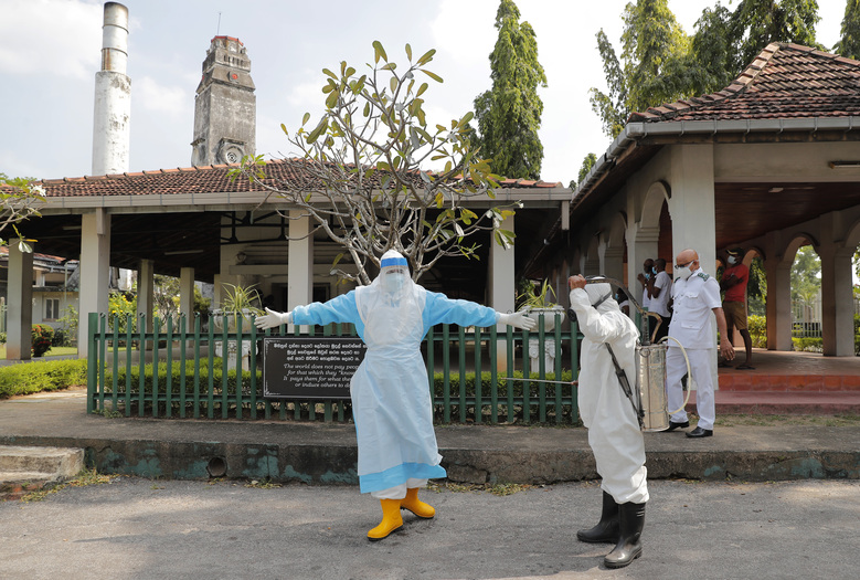 Sri Lankan health workers get disinfected after a cremation of COVID -19 victims at a cemetery in Colombo, Sri Lanka, Wednesday, Feb. 10, 2021. (AP Photo/Eranga Jayawardena)