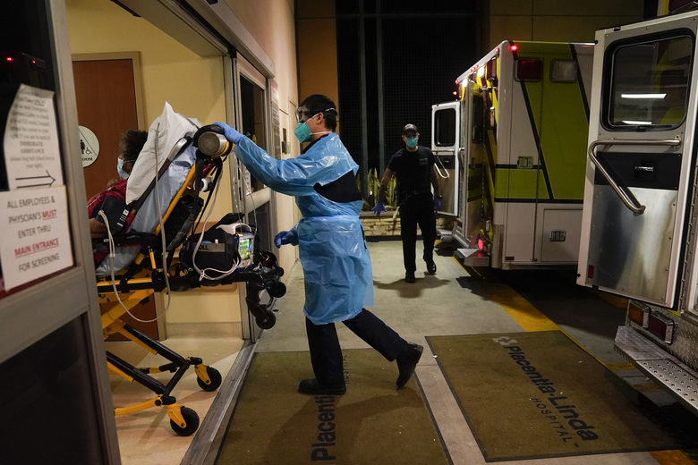 FILE – In this Jan. 8, 2021, file photo, emergency medical technician Thomas Hoang, 29, of Emergency Ambulance Service, pushes a gurney into an emergency room to drop off a COVID-19 patient in Placentia, Calif. Coronavirus hospitalizations are falling across the United States, but deaths have remained stubbornly high. (AP Photo/Jae C. Hong, File)