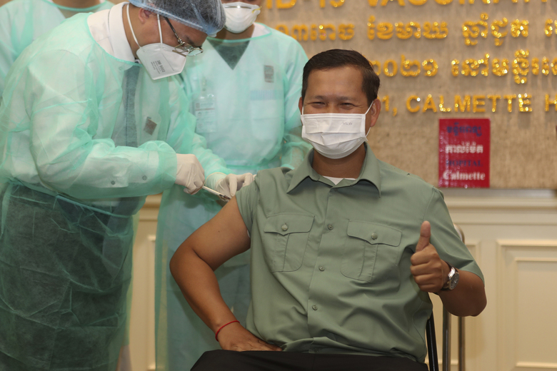 Cambodia's Lt. Gen. Hun Manet, a son of Prime Minister Hun Sen, receives a shot of the COVID-19 vaccine at Calmette hospital in Phnom Penh, Cambodia, Wednesday, Feb. 10, 2021. Cambodia began its inoculation campaign against the COVID-19 virus with vaccines donated from China, the country's closest ally. (AP Photo/Heng Sinith)