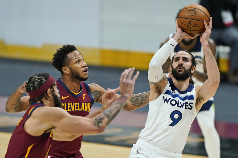 Minnesota Timberwolves' Ricky Rubio, right, shoots against Cleveland Cavaliers' JaVale McGee, left, and Lamar Stevens, center, in the second half of an NBA basketball game, Monday, Feb. 1, 2021, in Cleveland. (AP Photo/Tony Dejak)