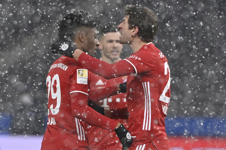 Bayern's Kingsley Coman, left, celebrates after scoring his side's opening goal during the German Bundesliga soccer match between Hertha BSC Berlin and FC Bayern Munich in Berlin, Germany, Friday, Feb. 5, 2021. (John MacDougall/pool via AP)