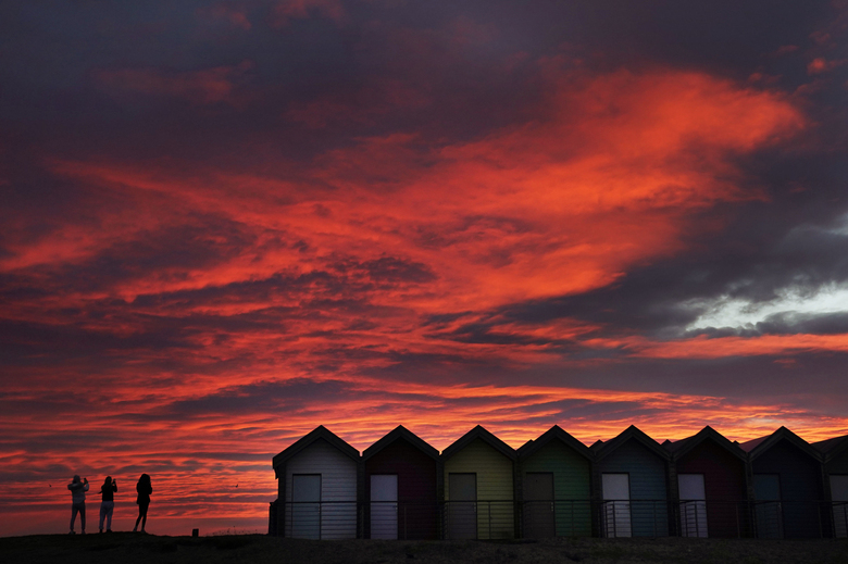 People take photos by colourful beach huts, in front of the red sky at sunrise in Blyth, Northumberland, England, Tuesday, Feb. 23, 2021. (Owen Humphreys/ PA via AP)