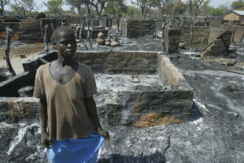 FILE – In this Monday, Feb 23, 2004 file photo, Anne, who declined to give her last name, stands in the remains of her burnt house in Barlonyo displaced persons camp in northern Uganda after a massacre committed by the Lord's Resistance Army (LRA). The International Criminal Court on Thursday, Feb. 4, 2021 convicted Dominic Ongwen, who was abducted by the shadowy Lord's Resistance Army militia as a 9-year-old boy and transformed into a child soldier and later promoted to a senior leadership rank, of dozens of war crimes and crimes against humanity ranging from multiple murders to forced marriages. (AP Photo/Karel Prinsloo, File)