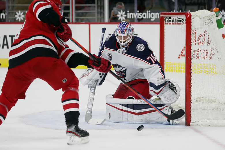 Columbus Blue Jackets goaltender Joonas Korpisalo (70) eyes the shot of Carolina Hurricanes' Cedric Paquette (18) during the second period of an NHL hockey game in Raleigh, N.C., Monday, Feb. 15, 2021. (AP Photo/Karl B DeBlaker)