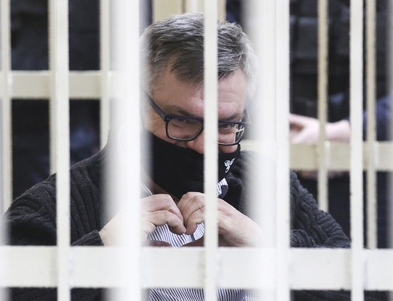 Viktor Babariko, the former head of Russia-owned Belgazprombank, gestures a heart symbol sitting in a cage in a court room in Minsk, Belarus, Wednesday, Feb. 17, 2021. Babariko, who had aspired to challenge President Alexander Lukashenko in a presidential election last August, has been jailed since May on money laundering and tax evasion charges that he has rejected as politically driven. (Oksana Manchuk/BelTA Pool Photo via AP)