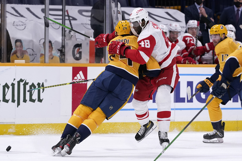Nashville Predators defenseman Jarred Tinordi (24) and Detroit Red Wings right wing Givani Smith (48) collide in the first period of an NHL hockey game Thursday, Feb. 11, 2021, in Nashville, Tenn. (AP Photo/Mark Humphrey)