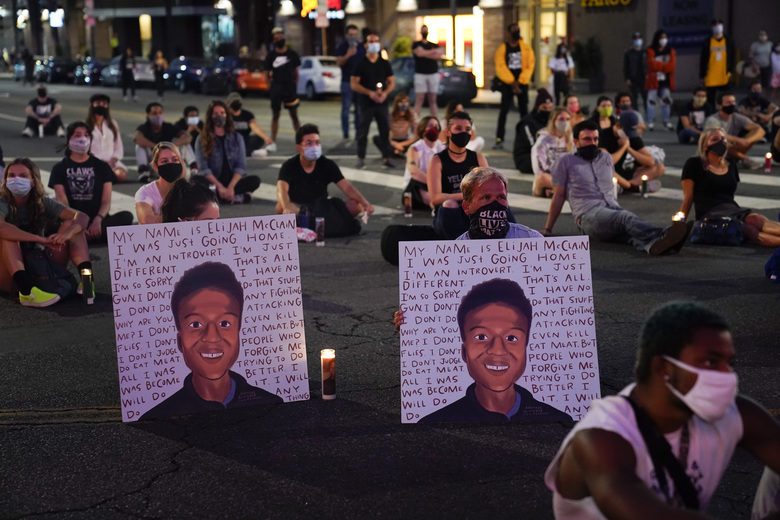 FILE – In this Aug. 24, 2020, file photo, two people hold posters showing images depicting Elijah McClain during a candlelight vigil for McClain outside the Laugh Factory in Los Angeles. An investigation into the arrest of McClain in suburban Denver criticizes how police handled the entire incident, faulting officers for their quick, aggressive treatment of the 23-year-old unarmed Black man and department overall for having a weak accountability system. (AP Photo/Jae C. Hong, File)