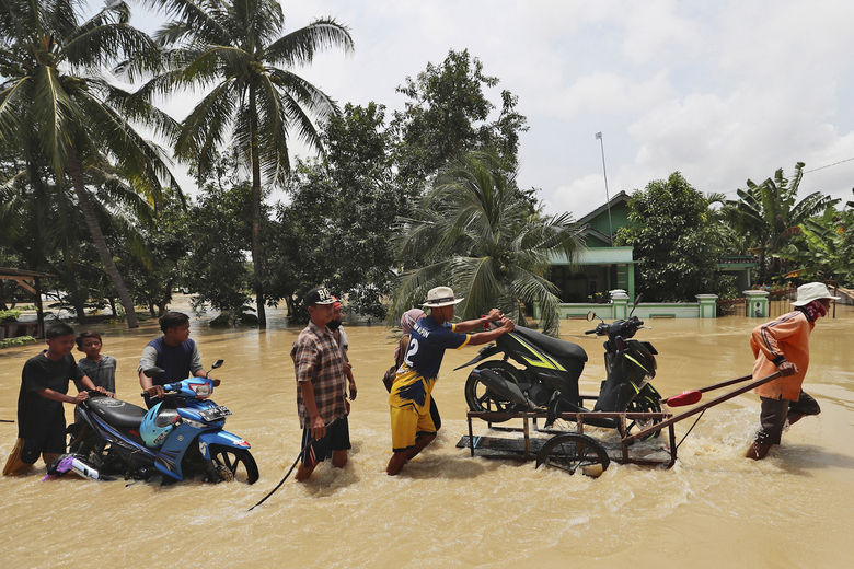 People push their motorcycles through an area flooded after the embankment of Citarum River burst, in Bekasi, Indonesia, Monday, Feb. 22, 2021. Heavy rains caused rivers to burst their banks in the region sending muddy water into residential and commercial areas, inundating thousands of homes. (AP Photo/Achmad Ibrahim)