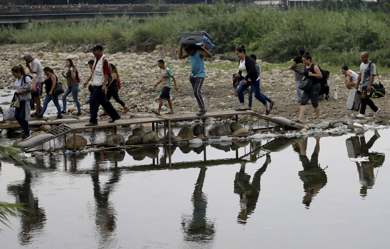 FILE – In this April 14, 2019 file photo, Venezuelans cross illegally into Colombia near the Simon Bolivar International Bridge, seen from La Parada near Cucuta, Colombia. President Ivan Duque said on Wednesday, Feb. 3, 2021, that Colombia needs greater cooperation from the international community to carry out a vaccination plan against COVID-19 for the estimated  million Venezuelan migrants without documents who are in the country, who are so far excluded from the new coronavirus vaccination plan. (AP Photo/Fernando Vergara, File)