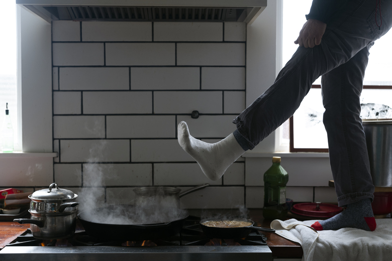 FILE – In this Feb. 16, 2021, file photo, Jorge Sanhueza-Lyon stands on his kitchen counter to warm his feet over his gas stove in Austin, Texas. Making decisions about risks — large or small — in the pandemic era is fraught enough. But the storms and outages ravaging Texas and other states have added a whole new layer to the process.  (AP Photo/Ashley Landis, File)
