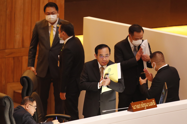 Thailand Prime Minister Prayuth Chan-ocha, third right, gestures to other parliament members after a no-confidence vote against him was defeated in Bangkok, Thailand Saturday, Feb. 20, 2021. Prayuth survived a no-confidence vote Saturday in parliament amid allegations that his government mismanaged the economy, bungled the provision of COVID-19 vaccines, abused human rights and fostered corruption. (AP Photo/Sakchai Lalit)
