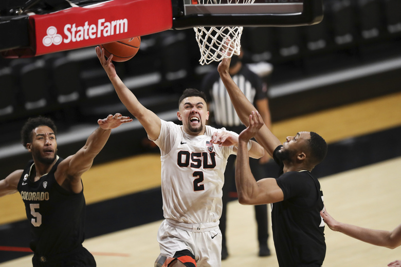 Colorado's D'Shawn Schwartz, left, and Dallas Walton, right, try to block a shot by Oregon State's Jarod Lucas during the first half of an NCAA college basketball game in Corvallis, Ore., Saturday, Feb. 20, 2021. (AP Photo/Amanda Loman)