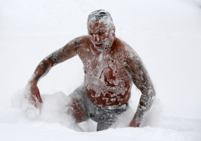 Enrico Ulbrich from Wernigerode bravely takes a dip in the fine powder snow in Wernigerode, Germany, Tuesday, Feb.9, 2021. The 41-year-old did not want to miss this fun with the huge amounts of snow in Wernigerode and romps around in the snow dressed only in a bathing suit. (Matthias Bein/dpa via AP)