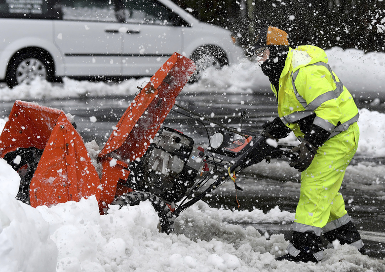 Mario Vieira, a custodian at the Beatrice H. Wood Elementary School in Plainville, Mass. struggles with a snowblower Tuesday, Feb. 2, 2021 while clearing sidewalks and walkways after the area received a blanket of wet, heavy snow overnight. (Mark Stockwell/The Sun Chronicle via AP)