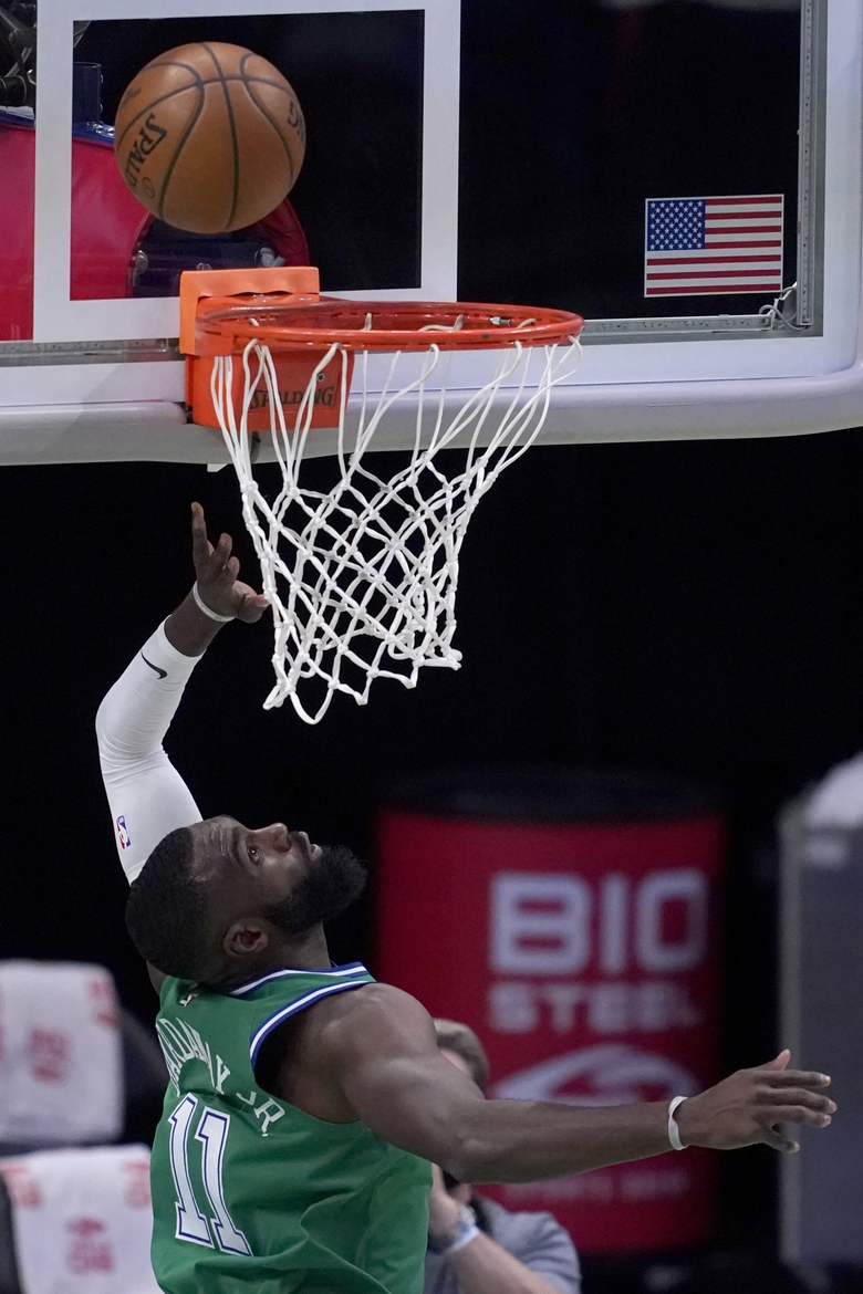 Dallas Mavericks' Tim Hardaway Jr. (11) looks up as his shot falls for a score in the first half of an NBA basketball game against the Memphis Grizzlies in Dallas, Monday, Feb. 22, 2021. (AP Photo/Tony Gutierrez)
