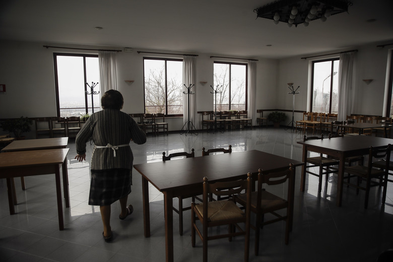 The owner of a restaurant walks through the dining room, in Vo Euganeo, northern Italy, Wednesday, Feb. 10, 2021. Shockwaves ran through the wine-making village of Vo', west of Venice, as word spread last Feb. 21 that a retired roofer had died of the new coronavirus becoming the first known COVID-19 victim in the West. (AP Photo/Luca Bruno)