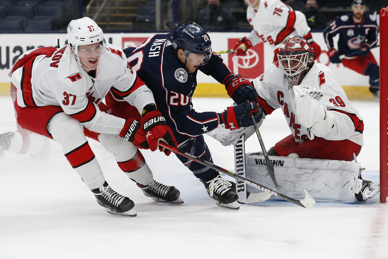 Carolina Hurricanes' Alex Nedeljkovic, right, makes a save as teammate Andrei Svechnikov, left, defends against Columbus Blue Jackets' Riley Nash during the second period of an NHL hockey game Monday, Feb. 8, 2021, in Columbus, Ohio. (AP Photo/Jay LaPrete)