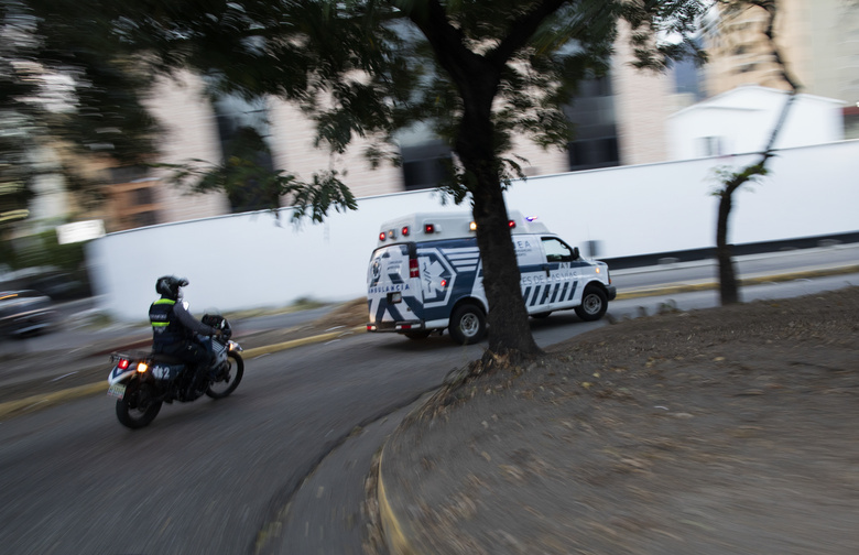 An Angels of the Road volunteer paramedic follows on a motorcycle their single ambulance transporting a patient who was injured in a road accident, in Caracas, Venezuela, Wednesday, Feb. 10, 2021. The volunteer group keeps a constant ear on walkie-talkie radio traffic and scan online chats dedicated to emergency services. (AP Photo/Ariana Cubillos)