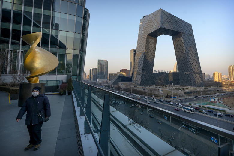 FILE – In this Feb. 4, 2021, file photo, a man wearing a face mask to protect against the spread of the coronavirus walks along an observation deck near the CCTV Headquarters building, the home of Chinese state-run television network CCTV and its overseas arm CGTN, in Beijing. China has banned the BBC World News television channel from the few outlets where it could be seen in the country in possible retaliation after British regulators revoked the license of state-owned Chinese broadcaster CGTN. (AP Photo/Mark Schiefelbein, File)
