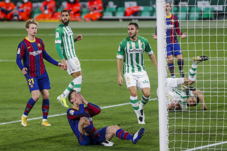 Barcelona's Clement Lenglet, foreground, reacts after missing a goal during La Liga soccer match between Betis and FC Barcelona at the Benito Villamarin stadium in Seville, Spain, Sunday, Feb. 7, 2021. (AP Photo/Miguel Morenatti)
