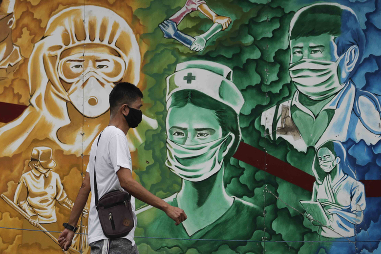 A man walks beside a mural of health workers outside the Mission Hospital in Pasig, Philippines, on Monday. (AP Photo/Aaron Favila)