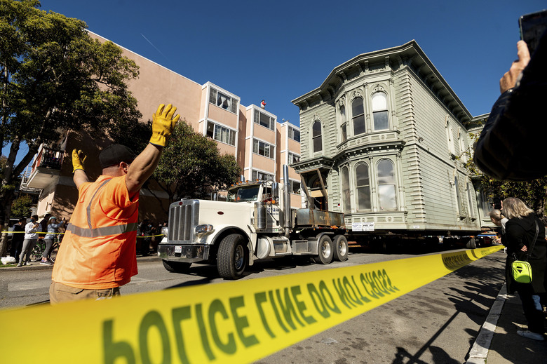 A worker signals to a truck driver pulling a Victorian home through San Francisco on Sunday, Feb. 21, 2021. The house, built in 1882, was moved to a new location about six blocks away to make room for a condominium development. According to the consultant overseeing the project, the move cost approximately $400,000 and involved removing street lights, parking meters, and utility lines. (AP Photo/Noah Berger)