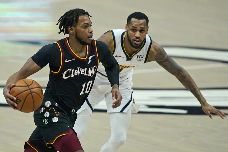 CORRECTS DENVER PLAYER TO MONTE MORRIS, INSTEAD OF WILL BARTON – Cleveland Cavaliers' Darius Garland, left, drives past Denver Nuggets' Monte Morris during the first half of an NBA basketball game Friday, Feb. 19, 2021, in Cleveland. (AP Photo/Tony Dejak)