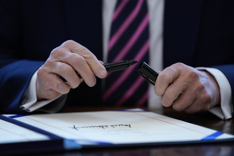 FILE – In this April 24, 2020, file photo President Donald Trump puts the cap on a pen after signing a coronavirus aid package to direct funds to small businesses, hospitals, and testing, in the Oval Office of the White House in Washington. (AP Photo/Evan Vucci, File)