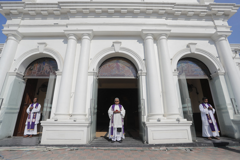 FILE- In this April 21, 2020 file photo, Sri Lankan Catholics priests stand at the entrance of St. Anthony's church, one of the sites of the 2019 Easter Sunday attacks, on the first anniversary of the deadly bombings in Colombo, Sri Lanka. Sri Lanka's Roman Catholic bishops said Monday that they are suspicious of the government's motives for not sharing with the church a presidential inquiry commission report into the 2019 deadly  Easter Sunday bomb attacks that killed more than 260 people,  and instead appointing a further committee to study it.(AP Photo/Eranga Jayawardena.File)