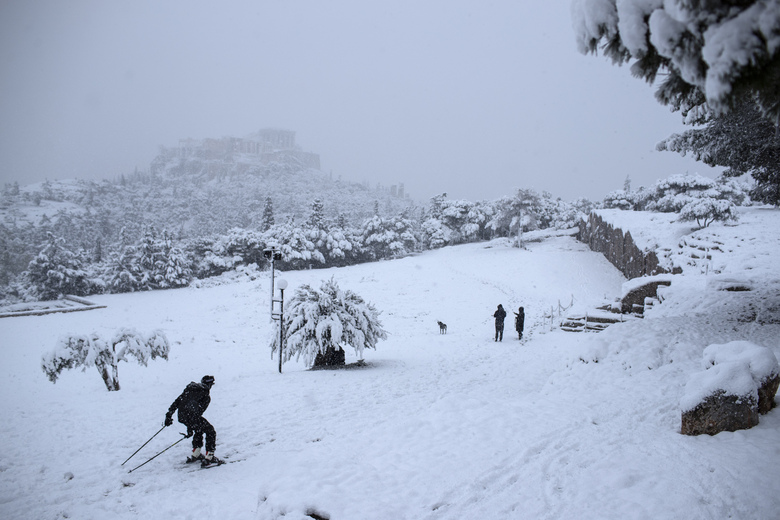 A man skis on snowy Pnyx hill in front the ancient Acropolis hill, near the ruins of the fifth century BC Parthenon temple, in Athens, Tuesday, Feb. 16, 2021. Unusually heavy snowfall has blanketed central Athens, with authorities warning residents particularly in the Greek capital's northern and eastern suburbs to avoid leaving their homes. (AP Photo/Petros Giannakouris)
