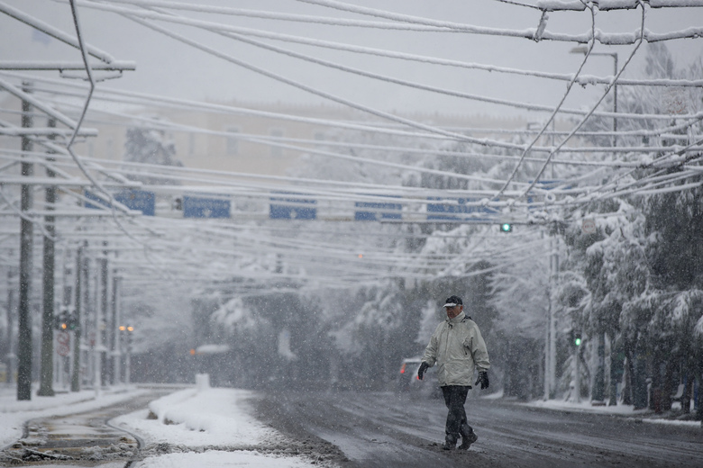 A man walks during a heavy snowfall in central Athens, Tuesday, Feb.16, 2021. Unusually heavy snowfall has blanketed central Athens, with authorities warning residents particularly in the Greek capital's northern and eastern suburbs to avoid leaving their homes. (AP Photo/Thanassis Stavrakis)