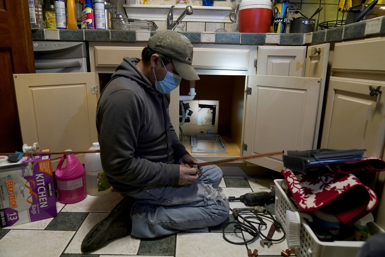 CORRECTS SPELLING OF LAST NAME TO VALERIO, NOT VALERIA – Handyman Roberto Valerio works on repairing a broken pipe beneath the sink in the home of Nora Espinoza, on Saturday, Feb. 20, 2021, in Dallas. The pipe broke during freezing temperatures brought by last week's winter weather. (AP Photo/Tony Gutierrez)